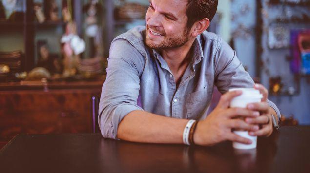 Das Bild zeigt einen Mann, der mit einem Kaffeebecher in der Hand am Tisch sitzt.