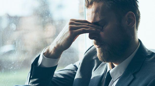 Das Bild zeigt einen Mann, der an Kopfschmerzen leidet.
