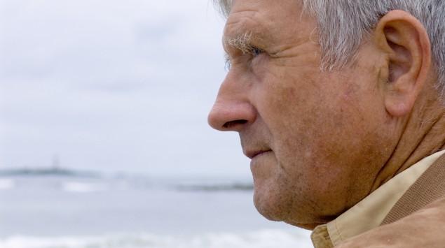 Ein alter Mann blickt auf das Meer.
