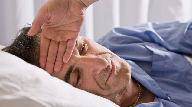 Man sieht einen Mann mit Fieber im Bett.
