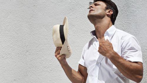 Das Bild zeigt einen Mann, der sich mit einem Hut Luft zufächelt.