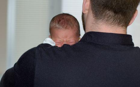 Ein Mann hält einen schreienden Säugling auf dem Arm.