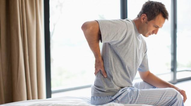 Ein Mann sitzt auf der Bettkante und fasst mit der rechten Hand an seinen Rücken.