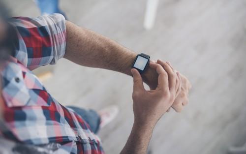 Ein Mann fummelt an seiner Smartwatch rum.