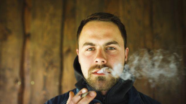 Das Bild zeigt einen jungen Mann beim Rauchen.