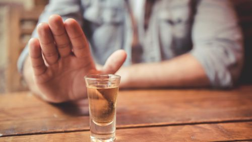 Ein Mann sitzt an einem Tisch, auf dem ein Schnapsglas steht, und hebt abwehrend die Hand.