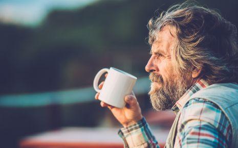 Das Bild zeigt einen älteren Mann, der eine Tasse in der Hand hält-