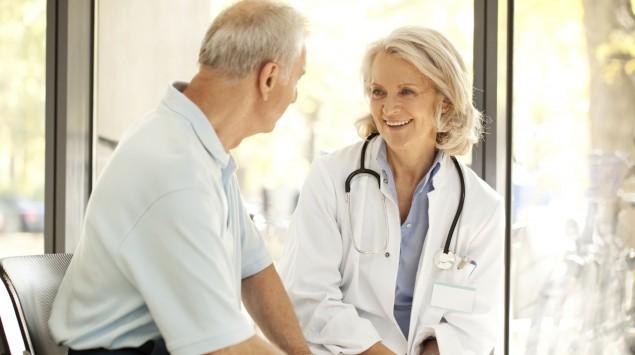 Eine Ärztin wendet sich lächelnd dem neben ihr sitzenden Mann zu.