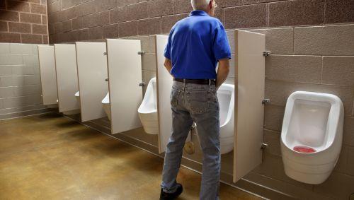 Das Bild zeigt einen älteren Mann, der ein Urinal benutzt.
