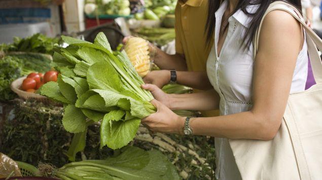 Man sieht Personen, die Gemüse auf einem Markt kaufen.