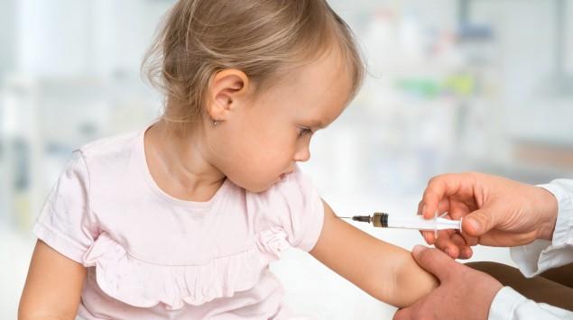 Das Bild zeigt ein junges Mädchen, dass gegen Masern geimpft wird.