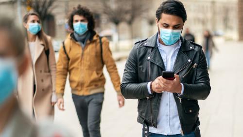 In einer Stadt sind mehrere junge Menschen zu Fuß mit Mund-Nasen-Schutz unterwegs.