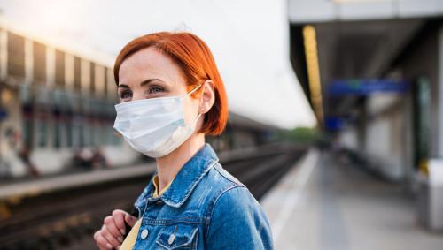 Eine rothaarige Frau mit Nasen-Mund-Maske steht wartend an einem Bahngleis.