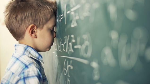 Das Bild zeigt einen kleinen Jungen, der an der Tafel steht und eine Matheaufgabe löst.