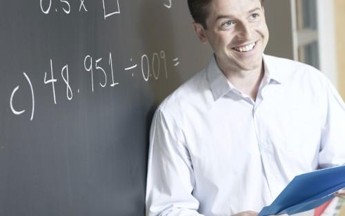Das Bild zeigt einen Lehrer vor einer Tafel.