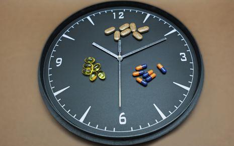 Man sieht eine Uhr und verschiedene Medikamente.