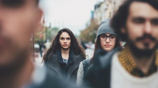 Mehrere junge Menschen sind in einer Stadt zu Fuß unterwegs.