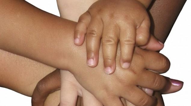 Mehrere unterschiedlich große und unterschiedlich farbige Hände liegen aufeinander.