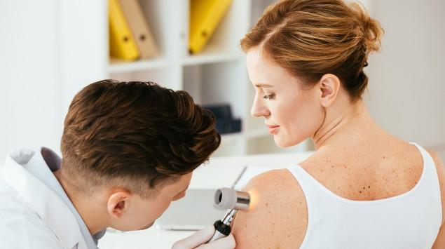 Hautarzt untersucht Muttermal einer Frau.