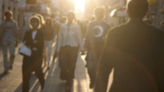 Eine Menschenmenge geht über eine von der Sonne beschienenen Straße.
