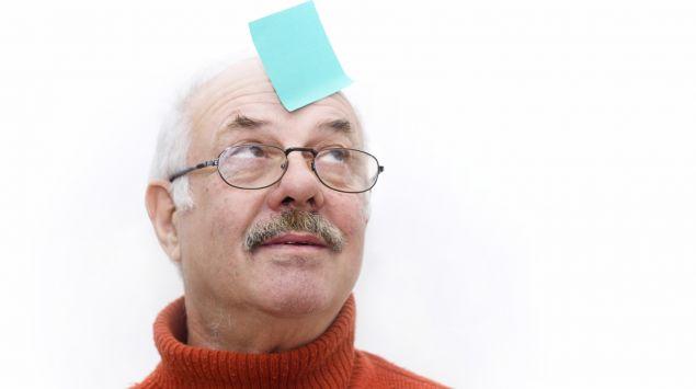 Ein älterer Mann mit einem auf die Stirn geklebten Merkzettel.