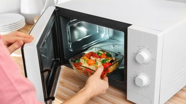 Jemand stellt ein Gemüse-Gericht in die Mikrowelle.