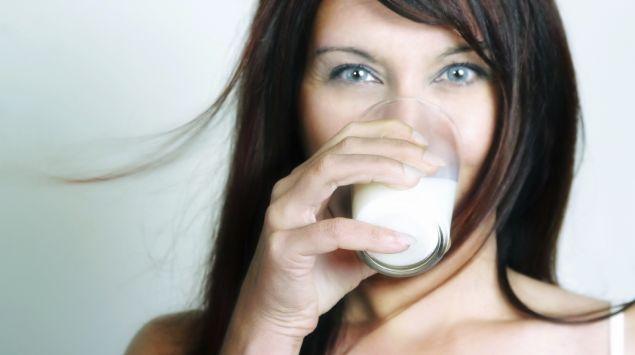 Eine brünette Frau trinkt ein Glas Milch.