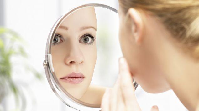 Junge Frau betrachtet ihr Gesicht im Spiegel.