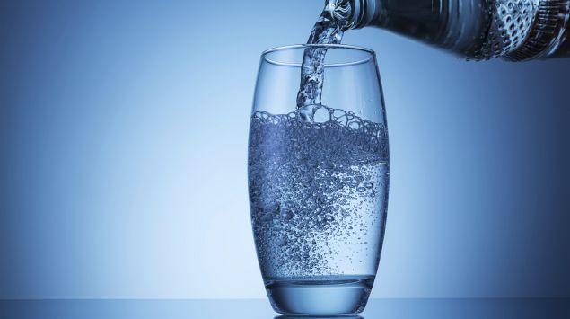 Mineralwasser fließt aus einer Flasche ins Glas.