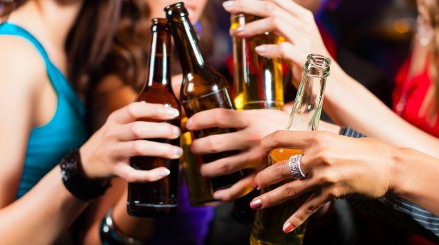 Eine Gruppe junger Leute stößt mit Bierflaschen an.
