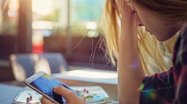 Ein Mädchen hält ein kaputtes Handy in der Hand.