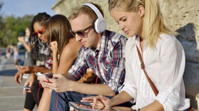 Eine Gruppe junger Leute nutzt verschiedene Mobilfunkgeräte.