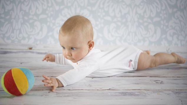 Baby greift in Bauchlage nach einem Ball.