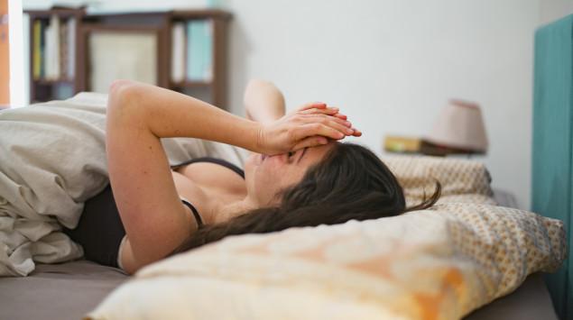 Eine Frau liegt im Bett und reibt sich müde die Augen.