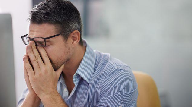 Ein Mann stützt das Gesicht in die Hände und schiebt dabei die Brille hoch.