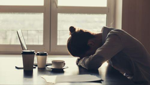 Das Bild zeigt eine Frau, die am Tisch sitzt und ihren Kopf auf den Unterarm stützt