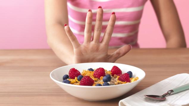Eine Frau lehnt mit einer Handbewegung eine Schale mit Früchtemüsli ab.
