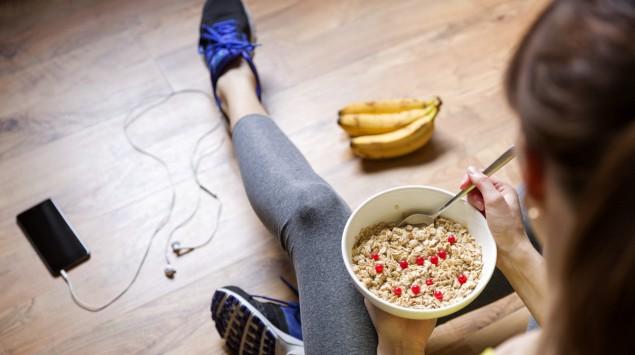 Eine junge Frau isst Müsli nach dem Sport.