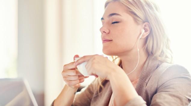 Man sieht eine entspannt wirkende Frau mit Kopfhörern.