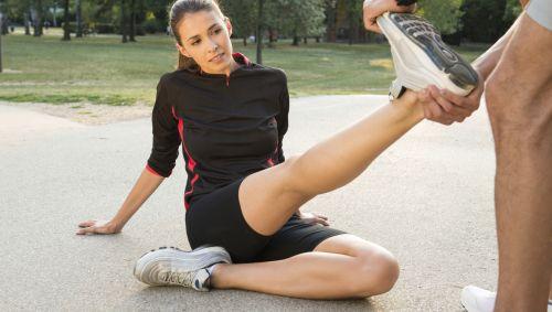 Ein Mann dehnt das Bein einer am Boden sitzenden Sportlerin
