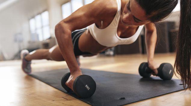 Muskeln trainieren: Das Bild zeigt eine Frau, die Liegestütz auf Hanteln macht.