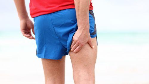 Das Bild zeigt einen Läufer am Strand, der sich den hinteren Oberschenkel hält.
