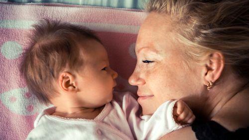 Eine Mutter kuschelt mit Ihrem Neugeborenen.