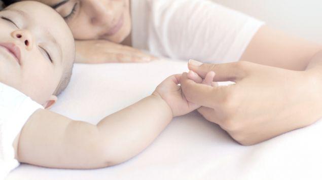 Eine Frau hält die Hand eines Babys.