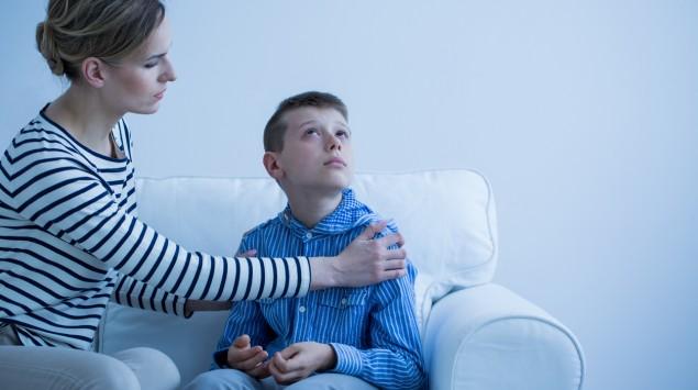 Eine Mutter will ihren Sohn trösten, dieser wendet sich ab.