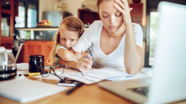 Eine Mutter sitzt angestrengt Schreibtisch, neben ihr ihre Tochter.