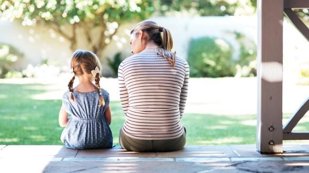 Rückansicht: Eine Mutter sitzt mit ihrer Tochter auf einer Treppe.
