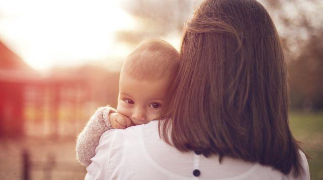 Ein Baby blickt über die Schulter der Mutter.