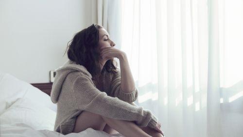 Eine Frau sitzt nachdenklich im Bett.