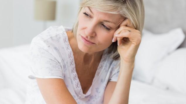 Eine Frau sitzt auf der Bettkante und blickt nachdenklich zur Seite.